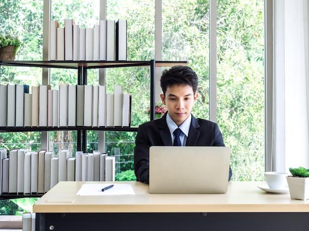 Junger asiatischer geschäftsmann im anzug, der mit laptop-computer im büro arbeitet