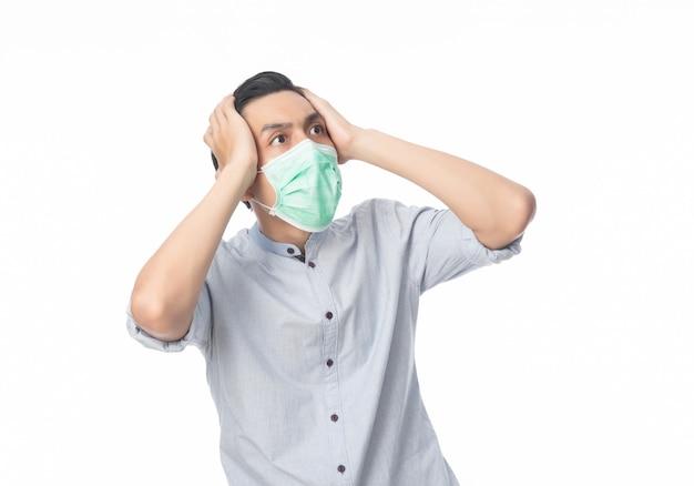 Junger asiatischer geschäftsmann in hygienemaskenschock, 2019-ncov oder coronavirus. atemwegserkrankungen in der luft wie pm 2.5-kämpfe. studioaufnahme lokalisiert auf weißer wand