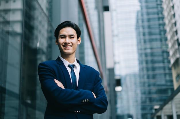 Junger asiatischer geschäftsmann mit glasgebäude