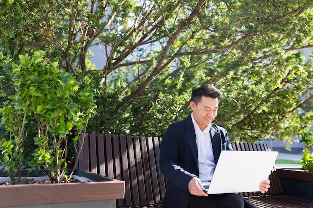 Junger asiatischer geschäftsmann oder freiberufler, der auf einer bank sitzt und mit laptop im stadtpark auf einem modernen städtischen straßenhintergrund im freien in der innenstadt arbeitet