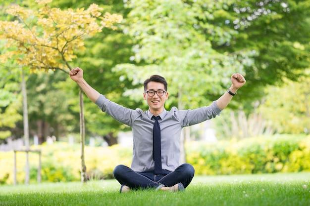 Junger asiatischer geschäftsmann unter verwendung der tablette, handy im park