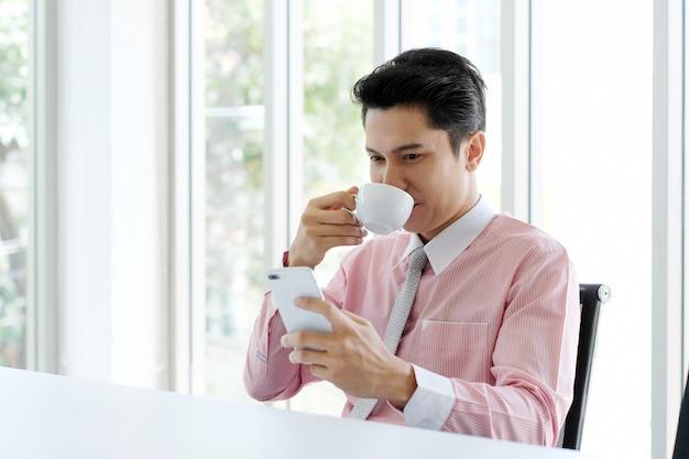 Junger asiatischer geschäftsmann unter verwendung des intelligenten telefons und des trinkenden kaffees im büro