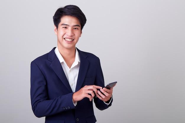 Junger asiatischer geschäftsmann unter verwendung eines intelligenten telefons