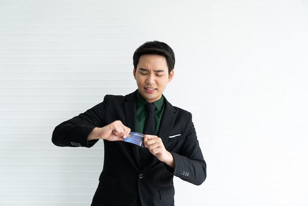 Junger asiatischer geschäftsmann versuchen, kreditkarte auf weiß zu zerstören