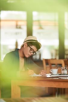 Junger asiatischer hippie, der im café sitzt und in notizbuch schreibt