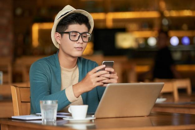 Junger asiatischer hippie-mann, der im café mit laptop sitzt und smartphone verwendet