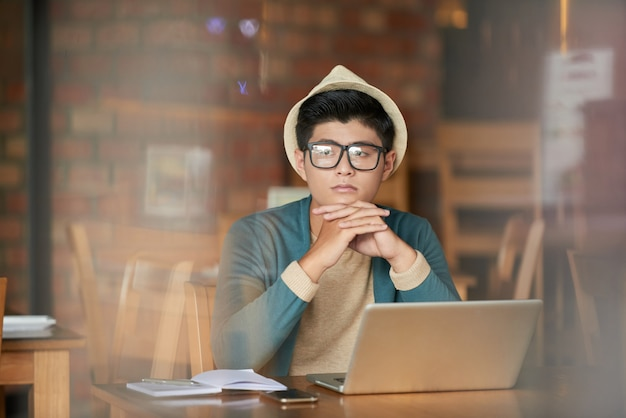 Junger asiatischer hippie-mann, der im café mit laptop sitzt und weg anstarrt