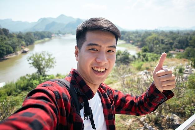 Junger asiatischer hipster-mann, der mit einem rucksack im sommerwaldreise-reiselebensstilkonzept reist