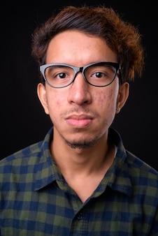 Junger asiatischer hipster-mann mit lockigem haar und akne gegen schwarzraum