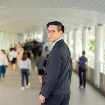 Junger asiatischer hübscher geschäftsmann mit seinen gläsern, die auf gehweg der modernen stadt stehen.