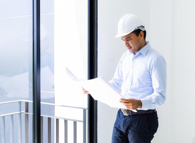 Junger asiatischer ingenieur oder architekten, die grundrissplan des gebäudes halten.