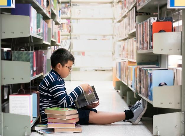 Junger asiatischer junge, der auf boden an den bibliothekslesebüchern sitzt.