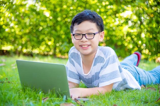 Junger asiatischer junge, der auf rasenfläche liegt und laptop-computer verwendet
