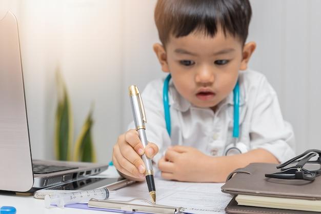 Junger asiatischer junge, der doktor spielt und auf diagnosediagramm schreibt.