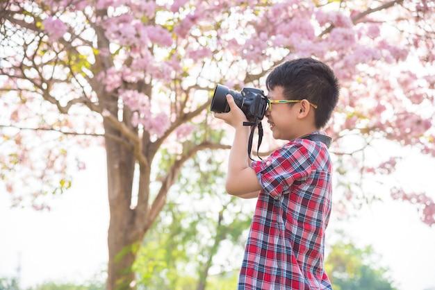 Junger asiatischer junge, der foto durch kamera im park macht