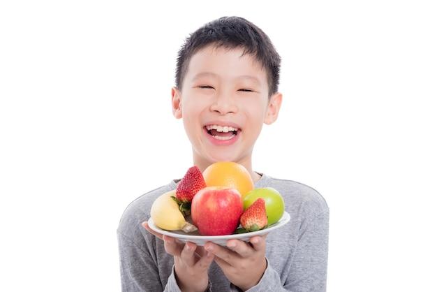 Junger asiatischer junge, der früchte und lächeln hält