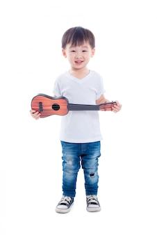 Junger asiatischer junge, der gitarrenspielzeug und -lächeln über weißem hintergrund hält