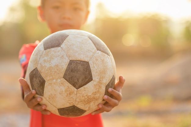 Junger asiatischer junge, der morgens mit altem und schmutzigem klassischem fußball spielt