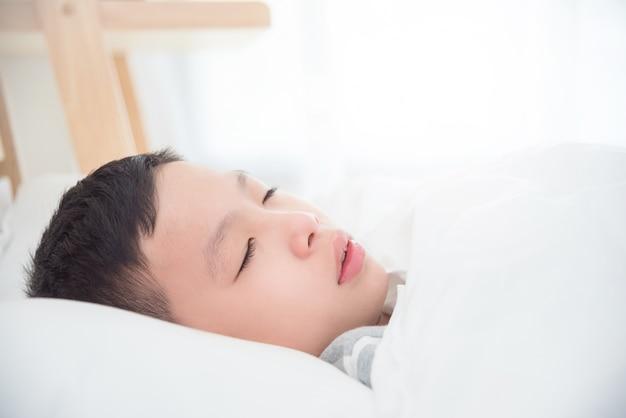 Junger asiatischer junge der nahaufnahme, der auf bett am morgen schläft