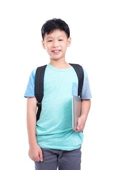 Junger asiatischer junge, der notebook und lächeln über weißem hintergrund hält