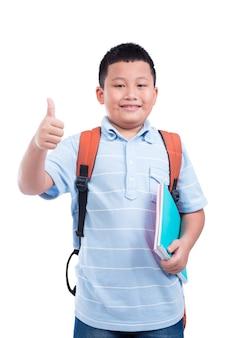 Junger asiatischer junge, der notizbuch hält und daumen oben über weißem hintergrund zeigt