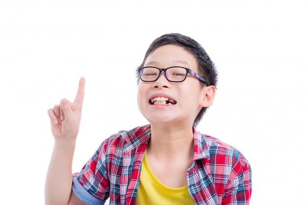 Junger asiatischer junge, der oben zeigt und über weißem hintergrund lächelt