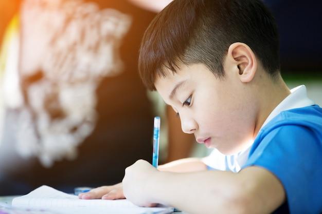Junger asiatischer junge, der seine hausarbeit tut