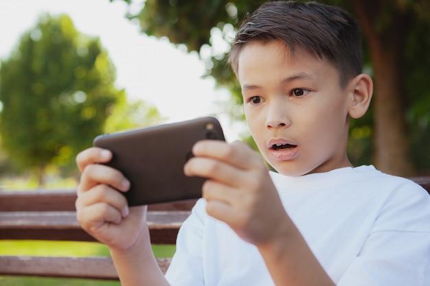 Junger asiatischer junge, der spiele an seinem intelligenten telefon am park spielt