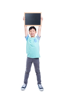 Junger asiatischer junge, der tafel und lächeln über weißem hintergrund hält