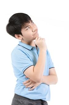 Junger asiatischer junge, der über weißem hintergrund denkt