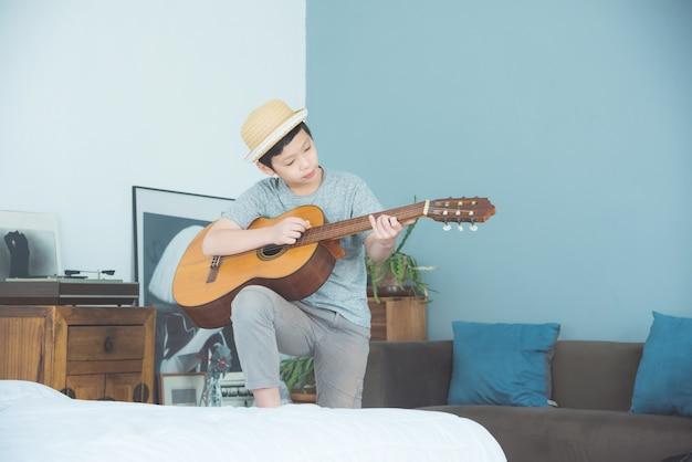 Junger asiatischer junge, der zu hause gitarre im wohnzimmer spielt