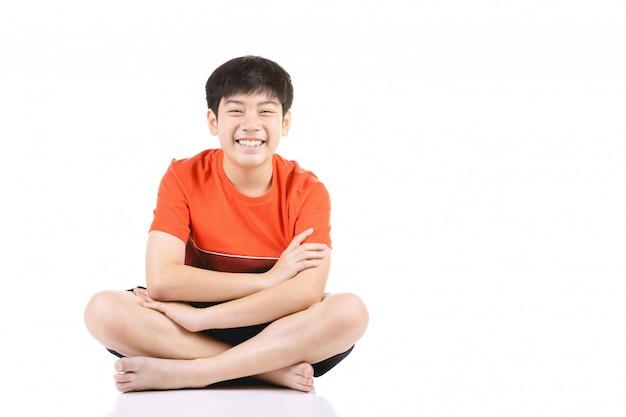 Junger asiatischer junge des porträts, der über weißem hintergrund sitzt,