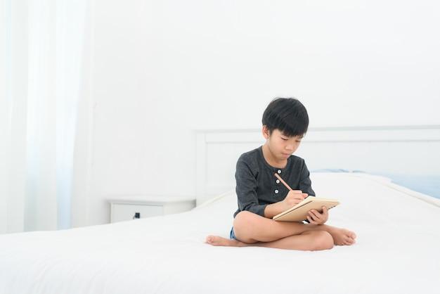 Junger asiatischer junge macht hausaufgaben auf einem bett zu hause