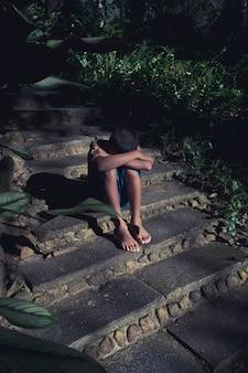 Junger asiatischer jungenaufenthalt alleine und traurigkeit