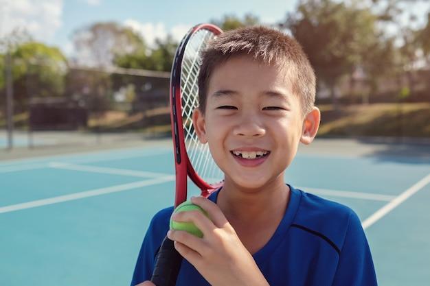 Junger asiatischer jungentennisspieler des tweens auf blauem gericht im freien