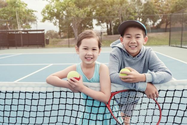 Junger asiatischer kindertennisspieler auf blauem gericht im freien