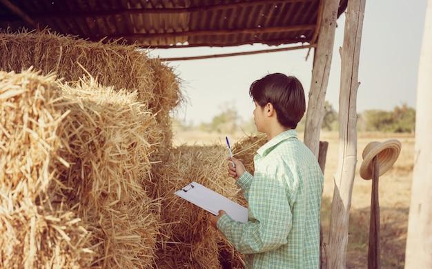 Junger asiatischer kluger bauernmann, der zwischenablage-checkliste hält, die ballen des gepressten strohs im ländlichen landspeicher prüft, kluges bauernkonzept