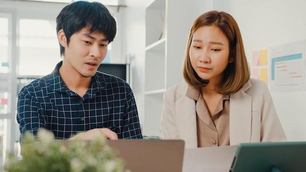 Junger asiatischer kreativer geschäftsmann und geschäftsfrau manager diskutieren projektvergleichspunkt in papierkram und laptop