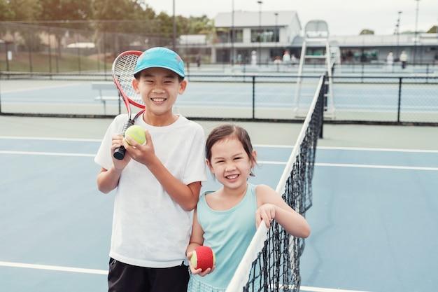 Junger asiatischer mädchen- und jungentennisspieler auf blauem gericht im freien