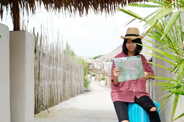 Junger asiatischer mädchenreisender, der karte hält und auf gepäck beim reisen in die landschaft im freien sitzt