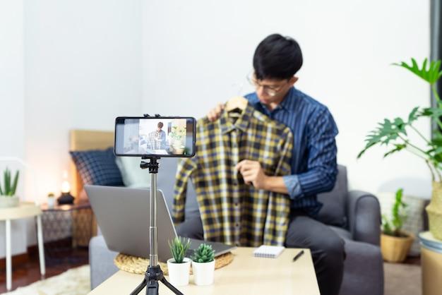 Junger asiatischer männlicher blogger, der vlog-video auf kamera-bewertung des produkts zu hause aufzeichnet, fokus auf stativ montierter kamerabildschirm überträgt live-stream-video an ein soziales netzwerk.