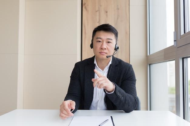 Junger asiatischer männlicher geschäftsmann, der online über videoanrufe, konferenzen oder treffen spricht und in die kamera schaut. webcam-ansicht. asia mann im anzug drinnen. büroverhandlungen distanz beratung oder beratung