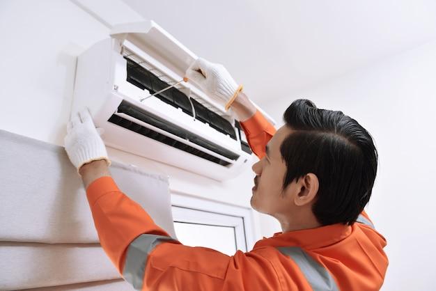 Junger asiatischer männlicher techniker, der klimaanlage mit schraubenzieher repariert