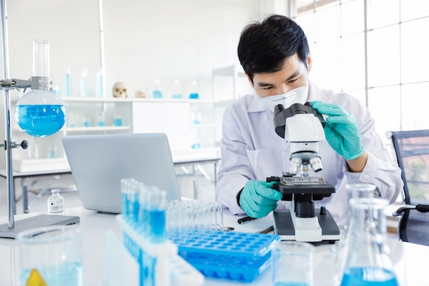 Junger asiatischer männlicher wissenschaftler, der durch die linse eines mikroskops schaut, während er innerhalb eines labors sitzt.