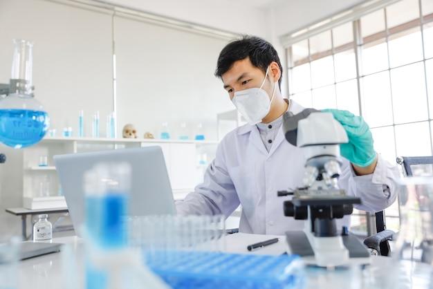 Junger asiatischer männlicher wissenschaftler, der notizen macht, während er durch ein mikroskop schaut und in einem labor sitzt