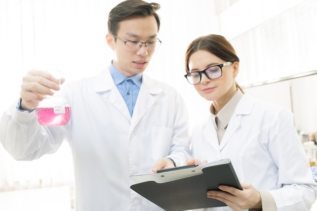Junger asiatischer männlicher wissenschaftler oder chemiker, der schnabel mit rosa flüssiger substanz hält, während er seinen assistenten bittet, seine merkmale aufzuschreiben
