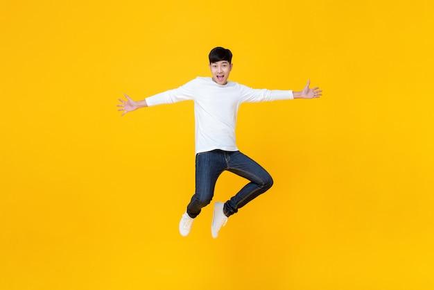 Junger asiatischer mann beim springen der zufälligen kleidung