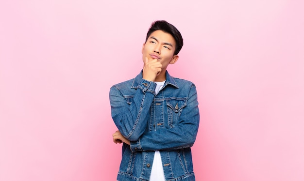 Junger asiatischer mann denkt, fühlt sich zweifelhaft und verwirrt, mit verschiedenen optionen, fragt sich, welche entscheidung über farbwand zu treffen ist