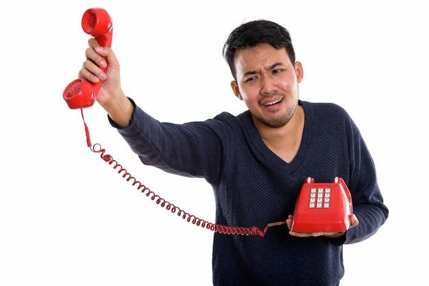 Junger asiatischer mann, der altes telefon hält, das verärgert schaut