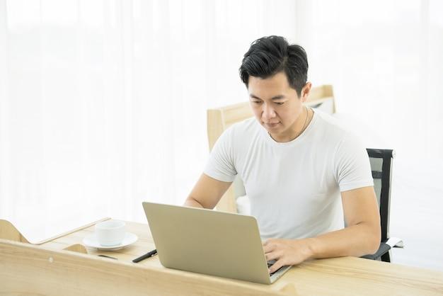 Junger asiatischer mann, der auf schreibtisch mit laptop und handy am sofa zu hause arbeitet.